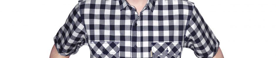 Джинсовая рубашка с коротким рукавом в среднюю бело серую клетку, с накладными карманами.Модель слегка зауженная с декоротивно подвернутыми рукавами
